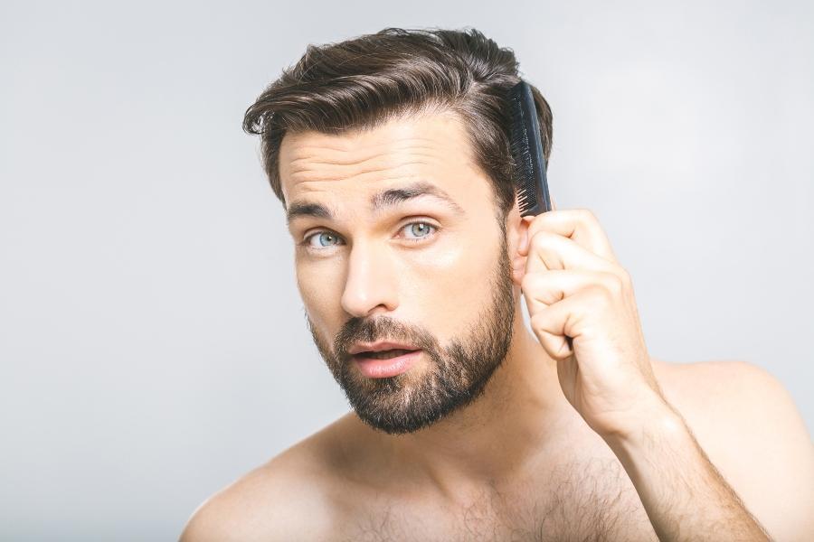 Mann kaemmt sein Haar im Badezimmer